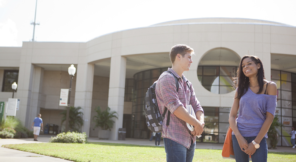 Male and female student talk about class outside the East Campus library