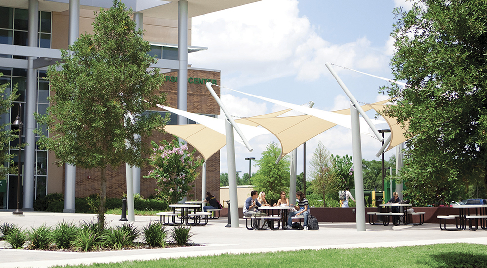West Campus students enjoy lunch under sun sails outside of West Campus Building 11.
